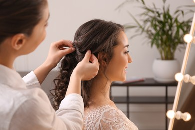 Stylist working with client in salon, making wedding hairstyle