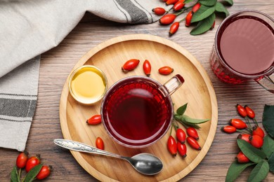Fresh rose hip tea, honey and berries on wooden table, flat lay