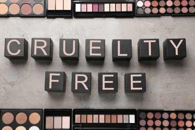 Flat lay composition with words Cruelty Free and eyeshadows not tested on animals against light grey stone background