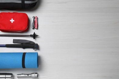 Flat lay composition with trekking poles and other hiking equipment on white wooden background, space for text