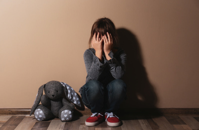 Abused little girl crying near beige wall. Domestic violence concept