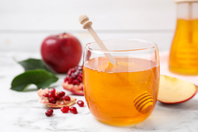 Honey, apples and pomegranate on white marble table, closeup. Rosh Hashanah holiday