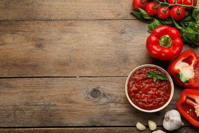 Delicious adjika sauce in bowl and ingredients on wooden table, flat lay. Space for text