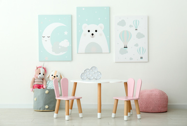 Adorable wall art, table and chairs with bunny ears in children's room interior