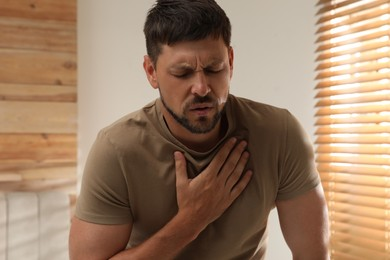 Man suffering from pain during breathing at home