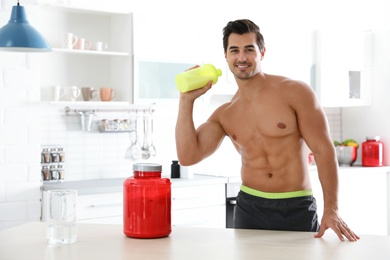 Young shirtless athletic man with protein shake powder in kitchen, space for text