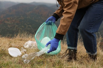 Woman with trash bag collecting garbage in nature, closeup