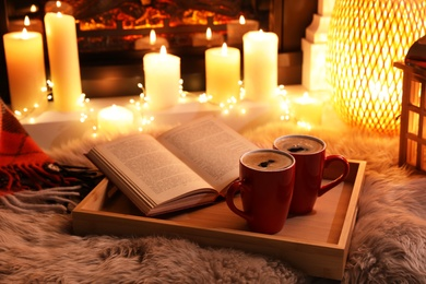 Cups of hot drink and open book near fireplace at home