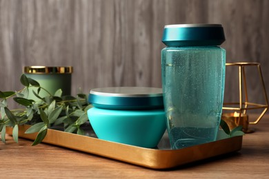 Hair care cosmetic products and green leaves on wooden table
