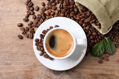 Cup of hot aromatic coffee and roasted beans on wooden table, flat lay