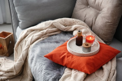 Aroma candles and oil on sofa in living room. Interior design