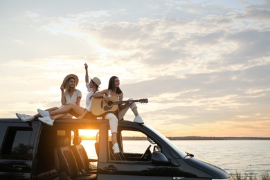 Happy friends with guitar sitting on car roof outdoors at sunset. Summer trip