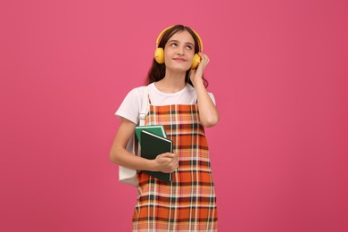 Teenage student with backpack, books and headphones listening to music on pink background