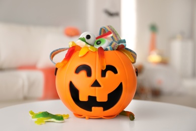 Halloween trick or treat bucket with different sweets on white table indoors
