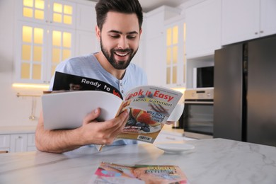 Young man with cup of drink reading magazine at table in kitchen