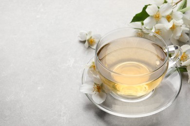 Glass cup of jasmine tea and fresh flowers on grey table. Space for text