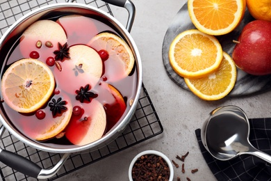 Delicious mulled wine and ingredients on grey table, flat lay