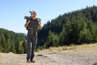 Man with backpack and sleeping mat in mountains. Space for text