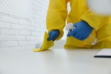 Employee in protective suit and gloves sanitizing table indoors, closeup. Medical disinfection