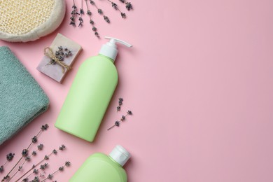 Flat lay composition with shower gel bottles and lavender flowers on pink background, space for text