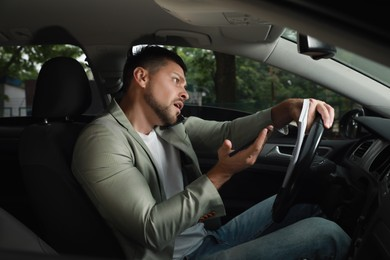 Stressed businessman talking on phone in driver's seat of modern car