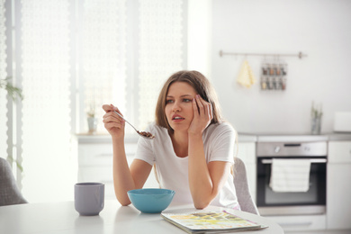 Sleepy young woman eating breakfast at home in morning