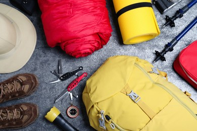 Flat lay composition with backpack and other camping equipment for tourism on grey background