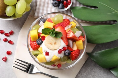 Delicious fruit salad on grey table, flat lay