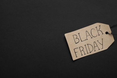 Black Friday tag on color background, top view. Space for text