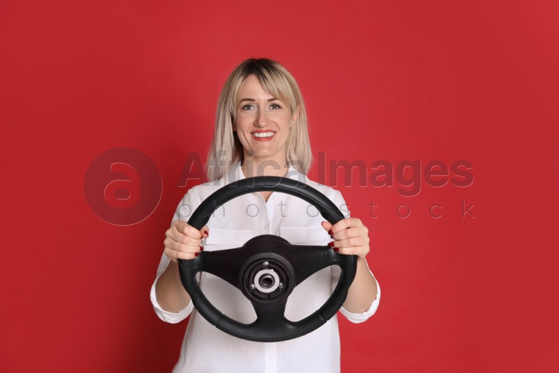 Happy woman with steering wheel on red background