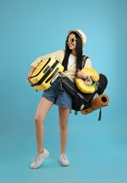 Happy female tourist with backpack, suitcase and travel pillow on light blue background