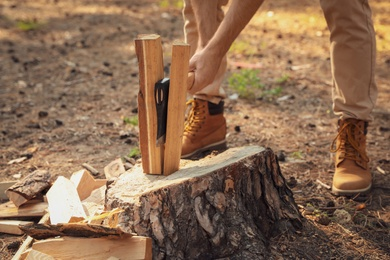 Man chopping firewood with axe in forest, closeup