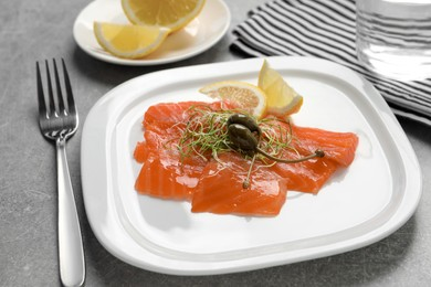 Salmon carpaccio with capers, microgreens and lemon served on grey table