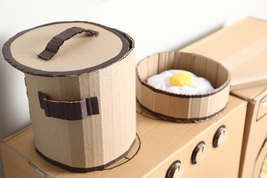 Cardboard stove with pot and frying pan near white wall