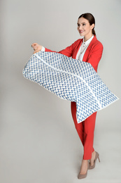 Young woman holding hanger with clothes in garment cover on light grey background. Dry-cleaning service