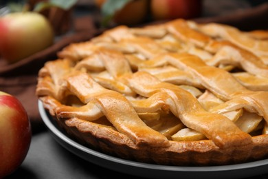 Delicious traditional apple pie on black table, closeup