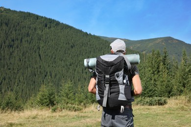 Man with backpack and sleeping mat in mountains, back view. Space for text