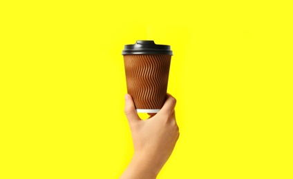 Woman holding takeaway paper coffee cup on yellow background, closeup