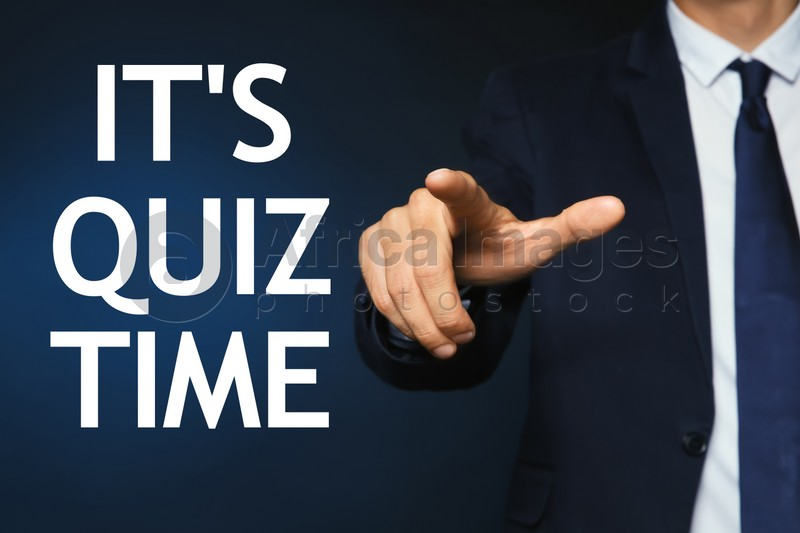 Man pointing at phrase IT'S QUIZ TIME on dark blue background, closeup view
