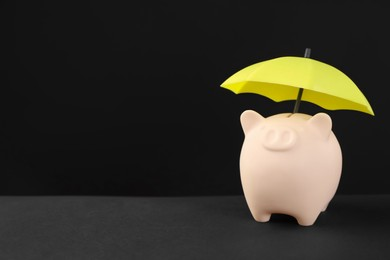 Small umbrella and piggy bank on black background. Space for text