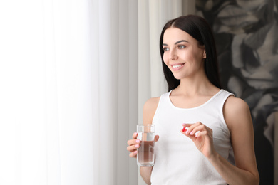 Woman with glass of water and vitamin capsule indoors. Space for text