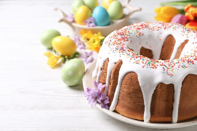 Glazed Easter cake with sprinkles, painted eggs and flowers on white wooden table. Space for text