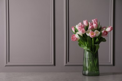 Beautiful bouquet of tulips in glass vase on grey table. Space for text