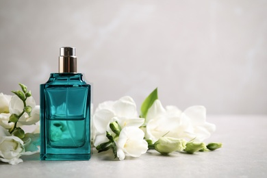 Bottle of perfume and beautiful flowers on light table. Space for text