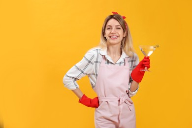 Young housewife with glass of martini on yellow background. Space for text