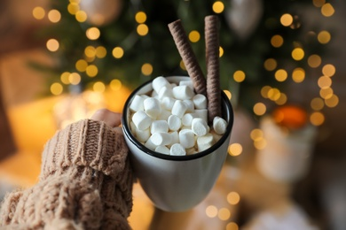 Woman with cup of cocoa indoors, closeup. Christmas mood