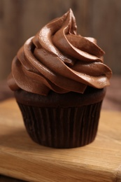 Delicious chocolate cupcake with cream on wooden board, closeup