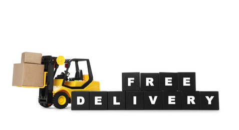 Toy forklift and cubes with words FREE DELIVERY isolated on white. Logistics and wholesale concept