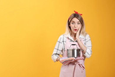 Young housewife with pot on yellow background. Space for text