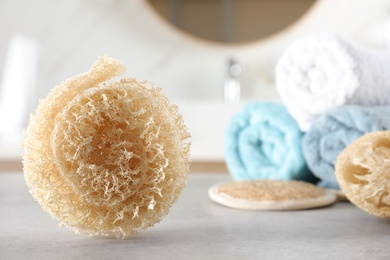 Natural loofah sponge on table in bathroom. Space for text